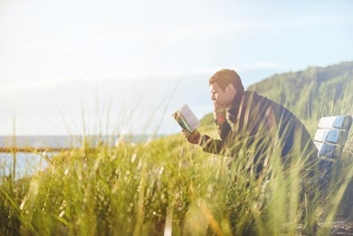 Man reading a book in the field