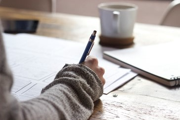 Person with pen writing notes