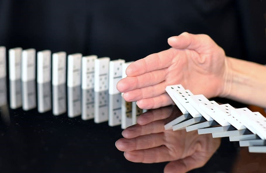 Hand stopping the domino effect halfway