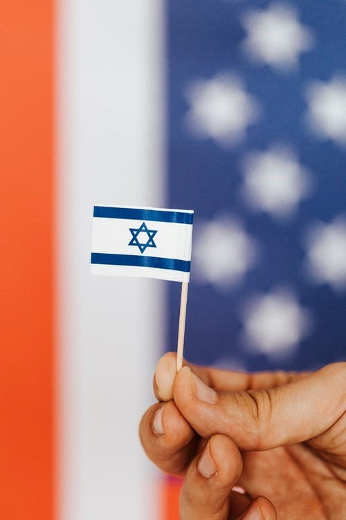 A person holding a miniature version of the Israel flag